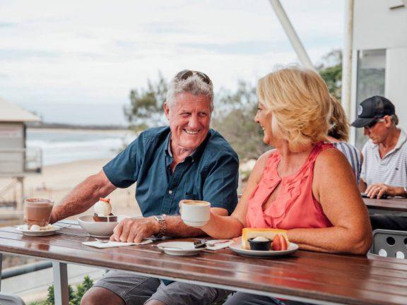 mooloolaba-surf-club-elderly-couple-on-deck-next-to-beach-drinking-coffee