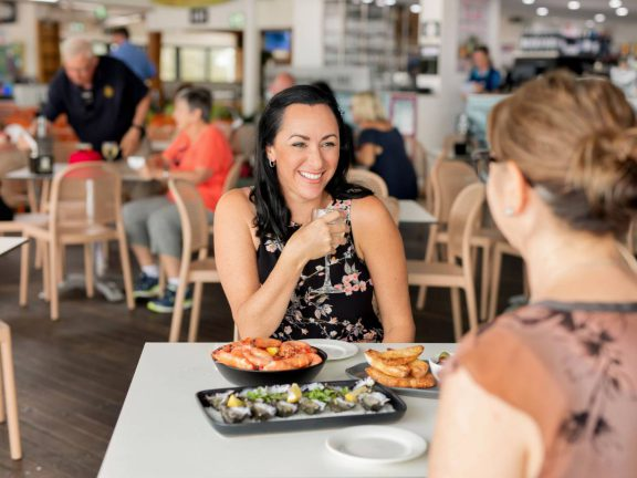 mooloolaba-surf-club-smiling-woman-holding-wine-prawns-and-oysters