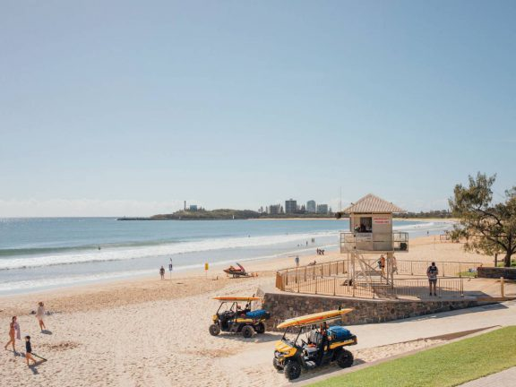 mooloolaba-surf-club-beach-view-with-surf-lifesaving-tower-and-vehicles