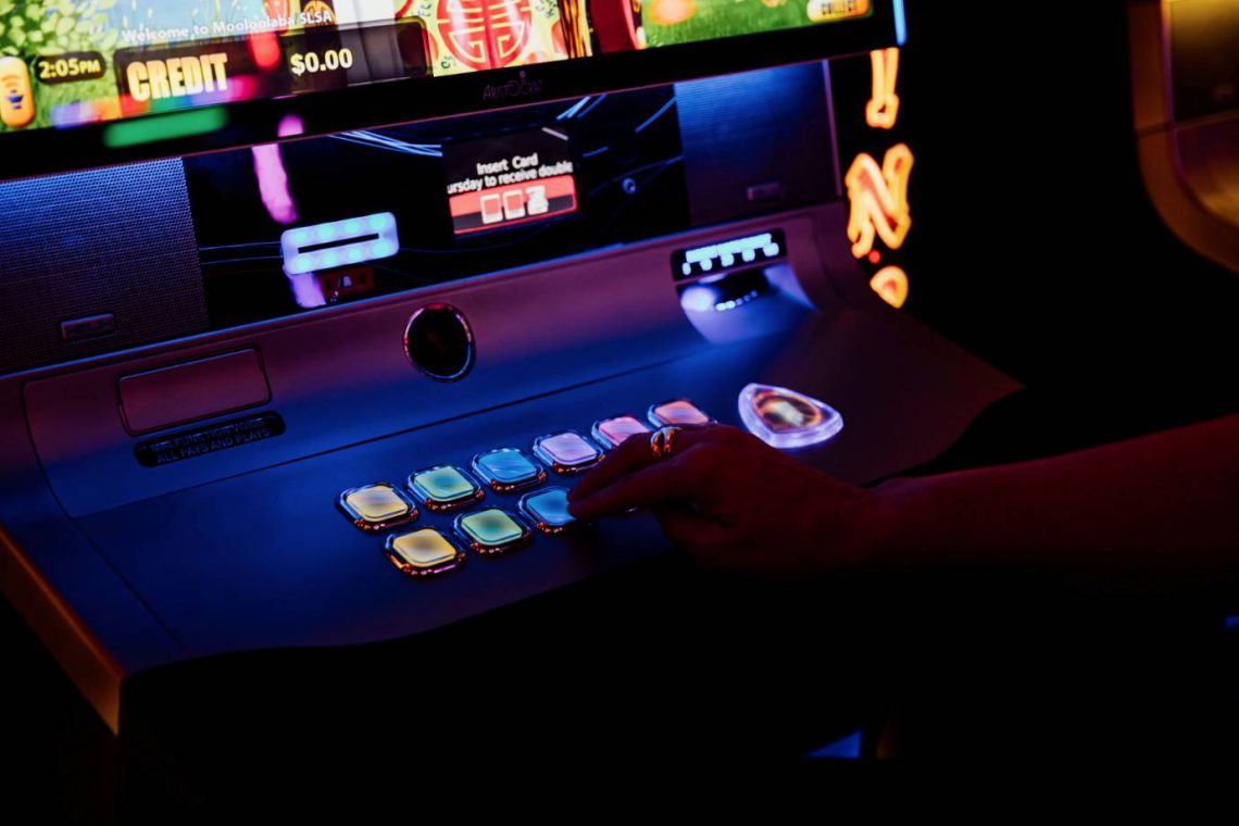 mooloolaba-surf-club-gaming-lounge-woman-pressing-buttons-on-poker-machine