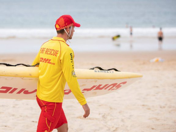 mooloolaba-surf-club-surf-lifesaving-member-with-board-on-beach