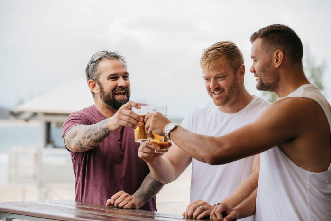 mooloolaba-surf-club-three-men-on-deck-saying-cheers-with-beer