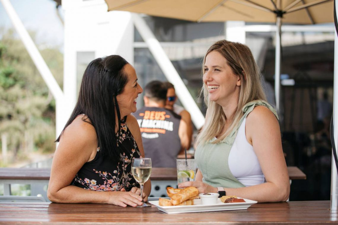 mooloolaba-surf-club-two-women-smiling-and-talking-on-deck